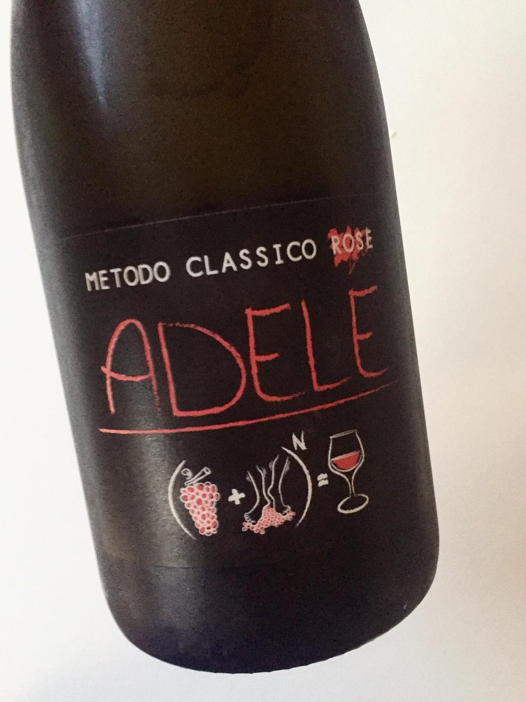 Bottiglia scura, il nome del vino sembra scritto con un pennarello rosso, Adele, in onore della figlia del vignaiolo. L'immagine è semplice, con dei simboli disegnati, un'addizione, l'uva ed il vignaiolo tra cui viene messo il più, danno il vino.