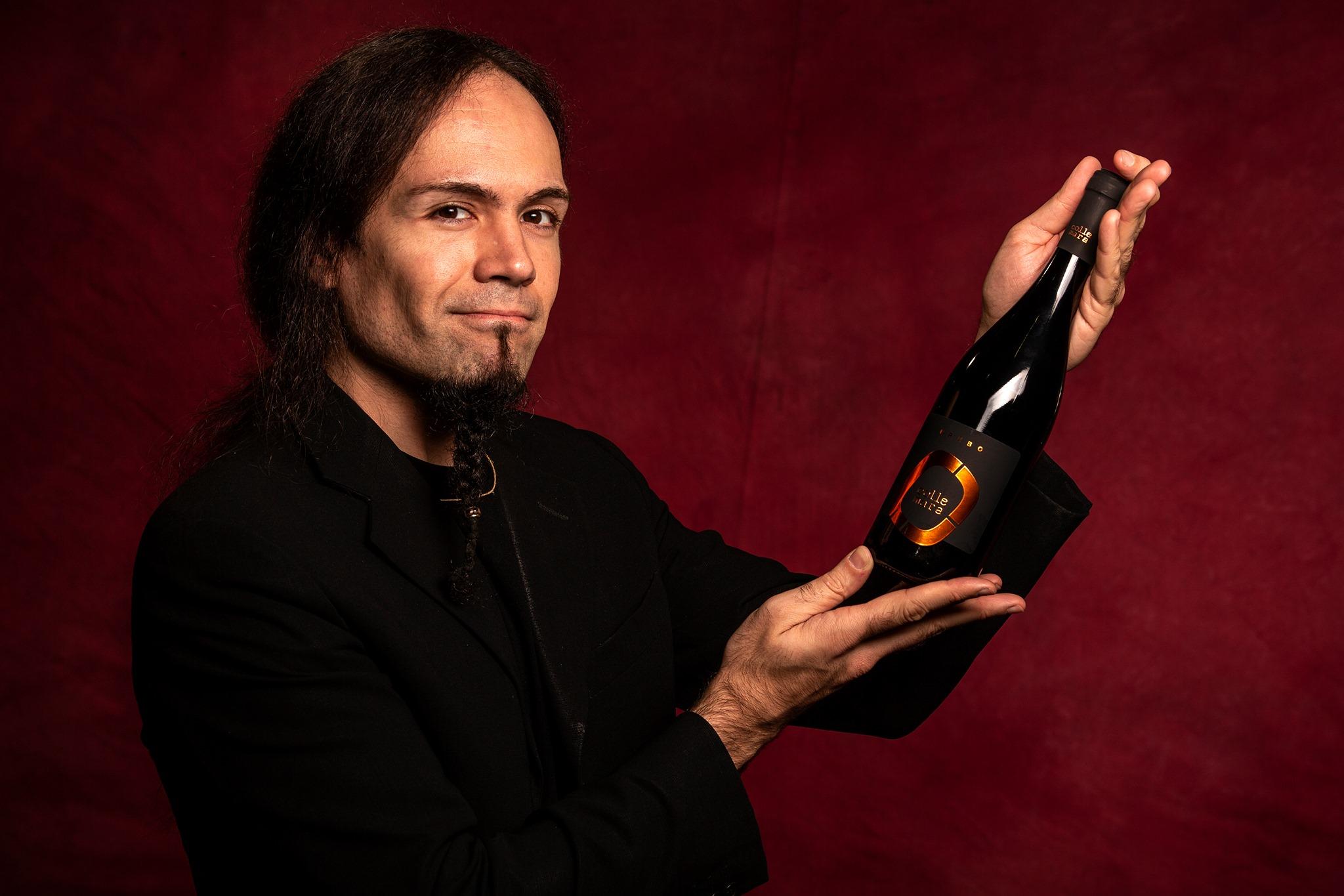 vini marchigiani Daniele Sartori, in look total black su sfondo rosso, mostra una delle bottiglie della collezione Collemara