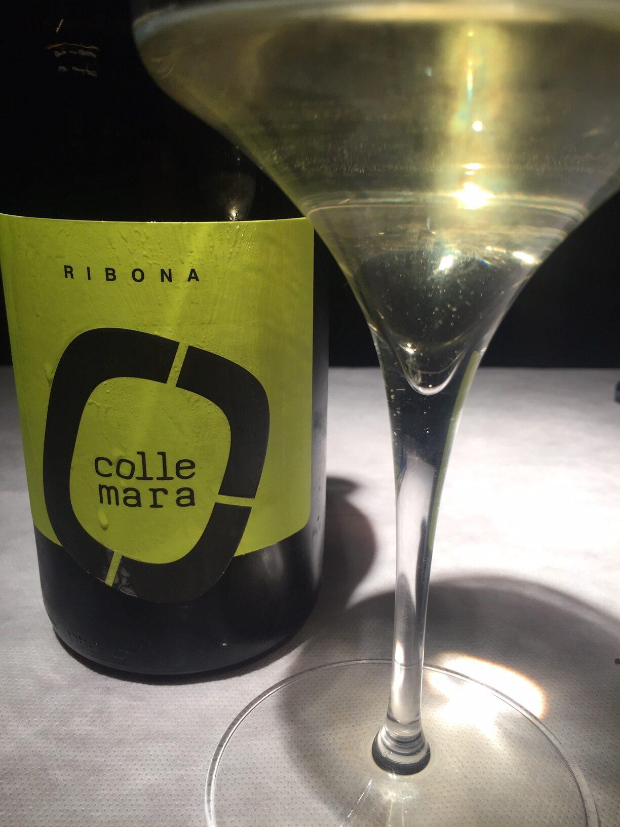Collemara, vino bianco Ribona della marche, etichetta giallo acido. Nel bicchiere un vino dai riflessi verdolini